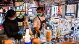 Bartender Gagan (kanan) dan seorang pelayan membersihkan bar jelang pembukaan kembali di New Delhi, 8 September 2020. Setelah sebelumnya ditutup karena pandemi COVID-19, mulai 9 September 2020 New Delhi mengizinkan bar kembali buka dengan kapasitas tempat duduk 50 persen. (Prakash SINGH/AFP)