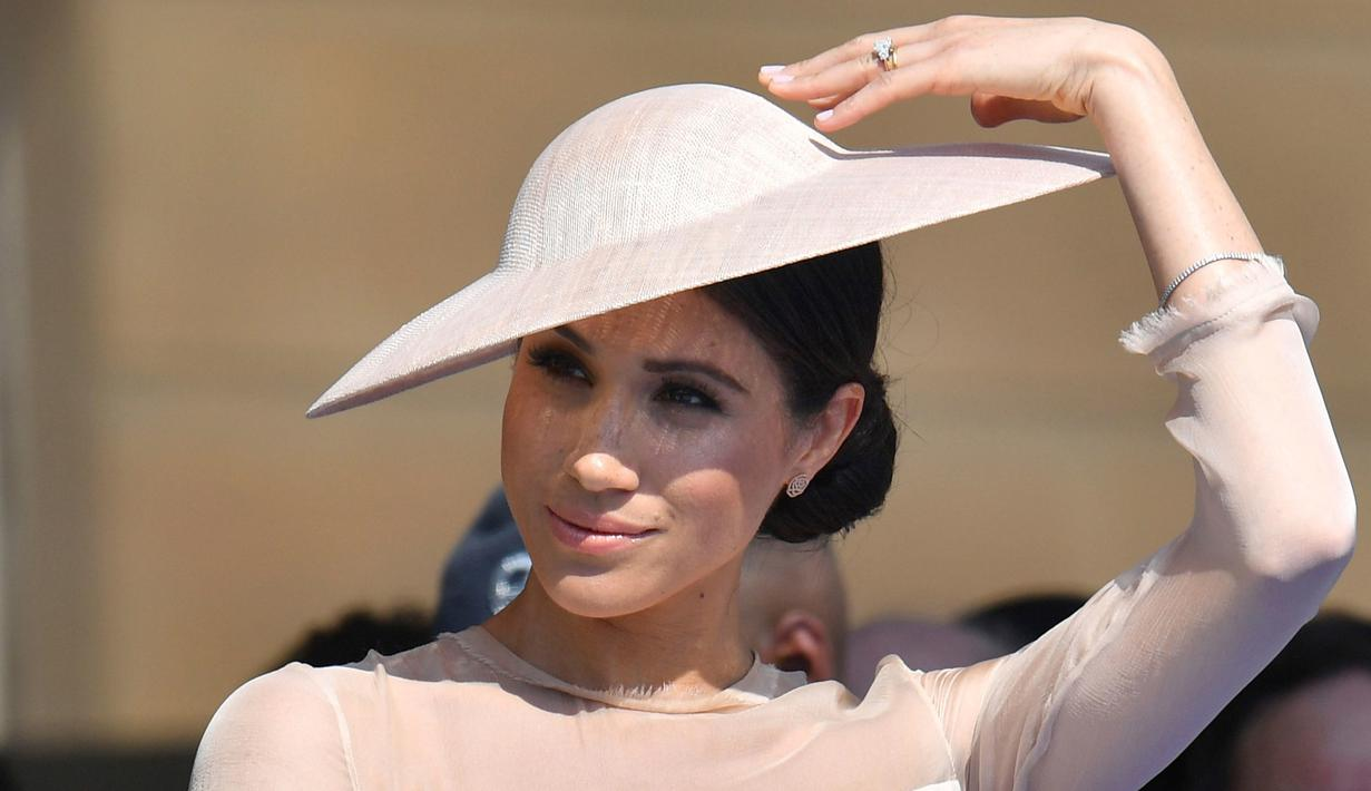 Duchess of Sussex, Meghan Markle menghadiri pesta kebun Istana Buckingham di London, Selasa (22/5). Tiga hari setelah pernikahannya dengan Pangeran Harry, Meghan tampil perdana di depan publik bersama sang suami. (Dominic Lipinski/Pool Photo via AP)