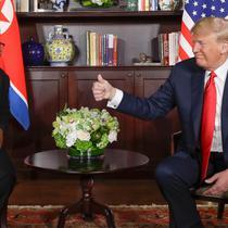Presiden AS Donald Trump  memberikan jempolnya seusai berjabat tangan dengan Pemimpin Korea Utara, Kim Jong-un dalam pertemuan bersejarah di resor Capella, Pulau Sentosa, Selasa (12/6). Trump dan Kim saling melemparkan senyum. (AP/Evan Vucci)