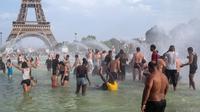 Turis dan warga masuk ke dalam kolam Trocadero Fountains (air mancur Trocadero) dekat Menara Eiffel di Paris, Kamis (25/7/2019). Gelombang panas di Eropa mencapai puncaknya, bahkan suhu di ibu kota Prancis mencapai di atas 41 derajat Celcius. (AP/Rafael Yaghobzadeh)