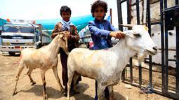 Anak-anak Yaman berpose dengan kambing di pasar ternak menjelang Idul Adha di ibu kota Sanaa, 6 Agustus 2019. Umat Islam di seluruh dunia akan merayakan Idul Adha yang identik dengan tradisi berkurban menggunakan hewan seperti kambing, domba, unta, sapi dan kerbau. (MOHAMMED HUWAIS/AFP)