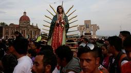 Sebuah patung Bunda dari Guadalupe diantara kerumunan peziarah di kawasan Basilika Guadalupe di Mexico City, Meksiko (11/12). Bunda dari Guadalupe adalah penampakan sosok Maria paling tua yang tercatat dalam sejarah agama Katolik. (Reuters/Henry Romero)