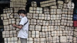 Pedagang berdiri di dekat Besek bambu yang dijual di kawasan Jatinegara, Jakarta, Senin (19/7/2021). Penurunan penjualan besek bambu akibat masih merebaknya Covid-19 serta berbagai larangan dalam aturan PPKM Darurat. (merdeka.com/Iqbal S. Nugroho)
