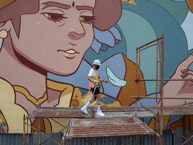 Muralis perempuan menyelesaikan pembuatan mural pada dinding di kawasan Juanda, Jakarta, Rabu (16/6/2021). Mural ini merupakan kegiatan kampanye Converese City Forests yang mengangkat tema Campaign Breaking Barries-True Color. (merdeka.com/Imam Buhori)