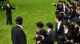 Seorang penggemar menirukan tingkah konyol Charlie Chaplin saat menggelar pertemuan di Corsier sur Vevey, Swiss, Minggu (16/4). Pertemuan yang dihadiri 662 orang itu dalam rangka merayakan HUT ke-128 Charlie Chaplin. (Laurent Gillieron/Keystone via AP)