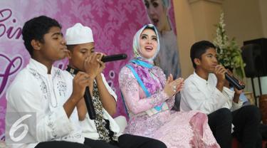 Penyanyi Syahrini saat buka puasa bersama dengan anak yatim piatu di Masjid Az-Zikra, Sentul, Bogor, Jumat (24/6). Syahrini berbagi rezeki dengan 5.000 anak yatim.  (Liputan6.com/Herman Zakharia)