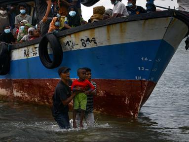 Nelayan Aceh membantu evakuasi seorang anak pengungsi etnis Rohingya menuju pesisir pantai desa Lancok, di Kabupaten Aceh Utara, Kamis (25/6/2020). Hampir 100 orang etnis Rohingya, termasuk 30 orang anak-anak ditemukan terdampar di tengah laut dengan kondisi kapal rusak. (CHAIDEER MAHYUDDIN/AFP)