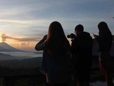 Wisatawan mengambil gambar sambil menikmati matahari terbit (sunrise) di Gunung Agung dari Kintamani, Bali, Rabu (13/12). BNPB menegaskan bahwa kondisi Pulau Bali aman bagi wisatawan meski Gunung Agung berstatus siaga. (AP Photo/Firdia Lisnawati)