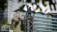 Pekerja memasang penyangga dan kawat baja pada Patung Selamat Datang di Bundaran HI, Jakarta, Jumat (25/3). Pemasangan tersebut bertujuan untuk menjaga patung dari goncangan ketika bor Antareja melintasi kawasan Bundaran HI. (Liputan6.com/Faizal Fanani)