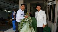 Wali Kota Surabaya Tri Rismaharini membagikan daun pisang untuk membungkus daging hewan kurban (Foto: Dok Humas Pemkot Surabaya)