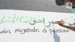 Remaja membuat mural bertema solidaritas untuk Palestina di Gang Jambu, Kedaung, Depok, Jawa Barat, Selasa (18/5/2021). Remaja Majelis Al Muntaqilin membuat mural tersebut sebagai solidaritas serta doa bagi umat muslim Palestina dan Masjid Al Aqsa atas serangan Israel. (merdeka.com/Arie Basuki)