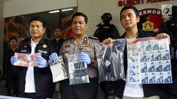 Kabid Humas Polda Metro Jaya Kombes Pol Argo Yuwono (tengah) menunjukkan barang bukti saat rilis tindak pidana pemalsuan atau pencurian data elektronik (skimming) di Polda Metro Jaya, Jakarta, Senin (19/3). (Liputan6.com/Arya Manggala)