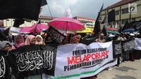 Massa Aliansi Umat Islam Pembela Tauhid Bogor dan Forum Muslim Bogor berunjuk rasa di halaman Polresta Bogor, Jawa Barat, Selasa (23/10). Massa membawa sejumlah bendera berwarna hitam dan putih bertulis kalimat syahadat. (Merdeka.com/Arie Basuki)