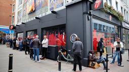 Orang-orang mengantre untuk memasuki toko andalan The Rolling Stones yang baru sebelum hari pertama pembukaannya di London, Rabu (9/9/2020). Toko tersebut akan menjual busana dan merchandise, serta musik, dari band rock The Rolling Stones. (Tolga Akmen / AFP)
