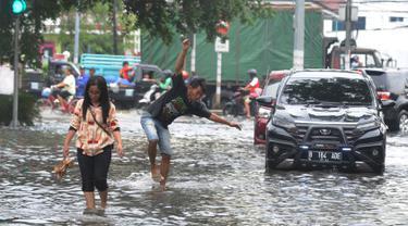 Warga dan kendaraan melintasi banjir di kawasan Green Garden, Jakarta Barat, Selasa (5/3). Sejumlah ruas jalan di Jakarta Barat tergenang air akibat luapan Kali Angke dan drainase yang buruk serta pasang air laut. (merdeka.com/Arie Basuki)