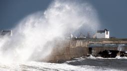 Gelombang ombak besar saat menghantam dermaga di depan sebuah rumah di Lesconil, Prancis barat (28/12/2020). Badai tersebut telah menyebabkan hujan deras, angin kencang dan ombak besar melanda pesisir Prancis. (AFP/Loic Venance)
