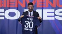 Pemain baru Paris Saint-Germain (PSG), Lionel Messi memegang kaus nomor 30 miliknya setelah pers konferensi di stadion Parc des Princes di Paris, Rabu (11/8/2021). Messi dikontrak oleh PSG selama dua tahun dengan opsi perpanjangan setahun di klub kaya Paris itu. (AP Photo/Francois Mori)