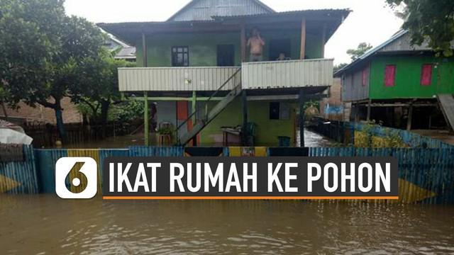 Banjir di Desa Bondra, Kabupaten Polewali Mandar, Sulawesi Barat meninggi. Warga mengikat rumah mereka dengan pohon agar tak terseret banjir.