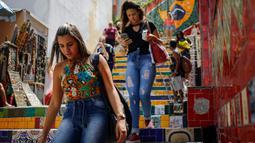 Pejalan kaki melintasi anak tangga yang terkenal dengan nama Selaron Steps atau Escadaria Selarón di Rio de Janeiro, Brasil pada 9 Desember 2019. Sang seniman pembuat yang bernama Jorge Selaron mempersembahkan karya seninya untuk rakyat Brasil. (Photo by David GANNON / AFP)