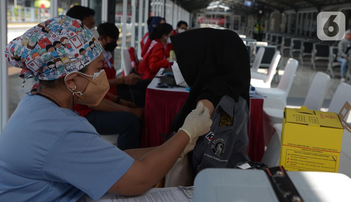 Tenaga kesehatan menyuntikkan cairan vaksin ke penumpang KRL Commterline serta  masyarakat umum  di Stasiun Kota, Jakarta, Rabu (28/7/2021). Vaksinasi disediakan 300 dosis bagi penumpang dan masyarakat umum guna menekan penyebaran Covid-19.  (merdeka.comm/Imam Buhori)