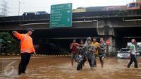 Warga membantu mendorong motor yang mogok saat berusaha menerobos banjir di Jalan Raya Kalimalang, Caman, Bekasi, Senin (20/2). Imbas banjir, ruas Jalan Kalimalang dari arah Jakarta menuju Bekasi dan sebaliknya ditutup (Liputan6.com/Gempur M Surya)