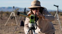 Seorang wanita menggunakan alat khusus bersiap untuk melihat gerhana matahari annular di Estancia El Muster, Argentina (26/2). Para astronom dan penyuka astronomi di Argentina berkumpul untuk menyaksikan gerhana matahari annular. (AFP/Alejandro Pagni)
