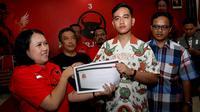 """Gibran Rakabuming mengenakan kemeja """"Indonesia Raya"""" saat mendaftar sebagai anggota kader PDIP di kantor DPC PDIP Solo.(Liputan6.com/Fajar Abrori)"""