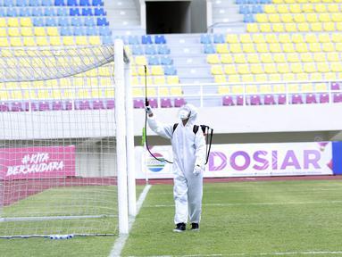 Petugas menyemprot jaring gawang dengan cairan disinfektan sebelum pertandingan antara Persikabo 1973 melawan Arema FC pada laga Piala Menpora di Stadion Manahan, Solo, Minggu (21/3/2021). (Bola.com/M Iqbal Ichsan)