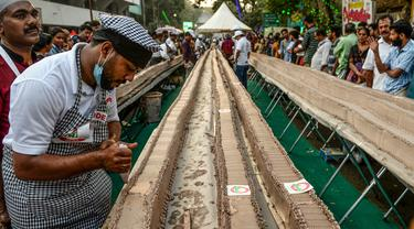 Seorang tukang roti menyelesaikan kue sepanjang 6,5 km untuk kue terpanjang dunia, di Thrissur di negara bagian Kerala, India selatan (15/1/2020). Ratusan pembuat roti dan koki di India selatan membuat kue terpanjang di dunia. (AFP/Arun Sankar)