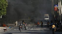 Polisi membersihkan barikade dari ban yang dibakar oleh pengunjuk rasa yang marah dengan meningkatnya kekerasan di lingkungan Lalue, Port-au-Prince, Haiti, Rabu (14/7/2021). Presiden Haiti Jovenel Moise dibunuh pada 7 Juli. (AP Photo/Fernando Llano)