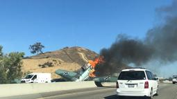 Kendaraan melintas di dekat pesawat antik Amerika Utara AT-6 yang terbakar di US 101 di Agoura Hills, California (23/10). AFP Photo/Cynthia Alvarez)
