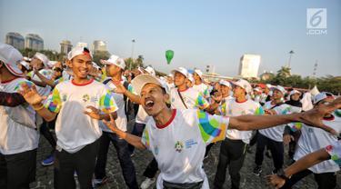 Warga mengikuti gerakan senam sembari menunggu prosesi Torch Relay Asian Games 2018 di Jakarta, Sabtu (18/8). Hari ini merupakan puncak kirab obor Asian Games 2018 dimana api abadi akan berlabuh di Gelora Bung Karno. (Liputan6.com/Faizal Fanani)