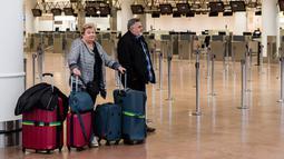 Dua penumpang menunggu informasi ketika mereka berada di Bandara Brussels, Zaventem, Belgia, Rabu (13/2). Penutupan lalu lintas udara Belgia dimulai sejak Selasa 12 Februari 2019 pukul 22.00 waktu setempat. (AP Photo/Geert Vanden Wijngaert)