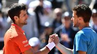 Dominic Thiem (kanan) mengalahkan Novak Djokovic pada semifinal Prancis Terbuka, Sabtu (8/6/2019). (AFP/Philippe Lopez)