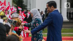 Presiden Joko Widodo (kanan) bersama Presiden Singapura, Halimah Yacob menyapa anak-anak berbaju daerah saat penyambutan kenegaraan di Istana Bogor, Jawa Barat, Selasa (4/3/2020). Halimah datang ke Indonesia bersama suaminya Mohamed Abdullah Alhabshee. (Liputan6.com/Faizal Fanani)