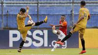 Pemain Bhayangkara Solo FC menghalau bola tembakan dari pemain Borneo FC Samarinda, Terens Owang Priska Puhiri (tengah), dalam pertandingan Babak Penyisihan Piala Menpora 2021 di Stadion Kanjuruhan, Malang. Senin (22/3/2021). (Bola.com/Arief Bagus)