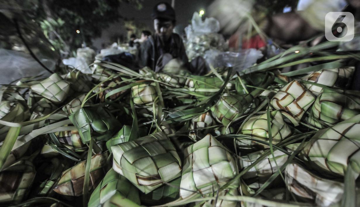 Aktivitas pedagang saat membuat bungkus atau tali ketupat di Pasar Klender, Jakarta Timur, Selasa (11/5/2021) malam. Menjelang Hari Raya Idul Fitri, Pasar Klender merupakan salah satu lokasi yang ramai dikunjungi warga untuk berburu ketupat, terutama saat malam hari. (merdeka.com/Iqbal S Nugroho)