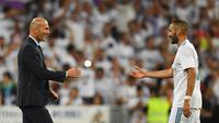 Pelatih Real Madrid, Zinedine Zidane, bersalaman dengan Karim Benzema usai mengalahkan Barcelona di Stadion Santiago Barnabeu, Rabu, (16/8/2017). Karim Benzema resmi memperpanjang masa bakti bersama Los Blancos hingga Juni 2021. (AFP/Gabriel Bouys)