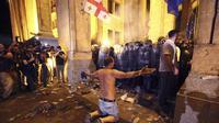 Seorang demonstran tampak berlutut di hadpaan polisi setelah bentrok menyebabkan 30 orang terluka (AP/ Zurab Tsertsvadze)
