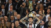Bek Juventus, Dani Alves mengangkat piala merayakan gelar Piala Coppa Italia di stadion Olimpico, Roma, (18/5). Alves mencetak gol di pertandingan ini dan mengantar Juventus meraih trofi Coppa Italia tiga kali berturut-turut. (AFP Photo/Andreas Solaro)