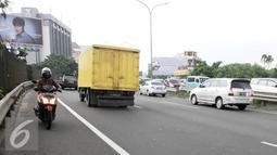 Pengendara motor melintas melawan arus jalan tol arah Merak dari persimpangan Taman Anggrek, Jakarta (4/2). Minimnya rambu-rambu lalulintas jalan menuju tol Merak membuat pengendara motor tidak mengetahuinya. (Liputan6.com/Helmi Afandi)