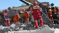 Tim SAR mencari korban yang tertimbun reruntuhan bangunan Masjid Jamiul Jamaah di Bangsal, Lombok Utara, Rabu (8/8). Bagian utara Lombok hancur oleh gempa pada Minggu malam dan merusak ribuan bangunan serta menewaskan banyak orang. (AP/Tatan Syuflana)
