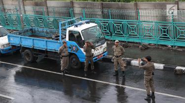 Personel Satpol PP foto bersama saat berjaga di sekitar trotoar kawasan Senen, Jakarta, Kamis (22/11). Penjagaan itu menyebabkan trotoar di kawasan Senen bebas dari PKL yang biasa berjualan pakaian bekas. (Liputan6.com/Immanuel Antonius)