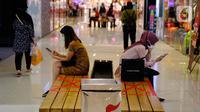 Pengunjung bermain ponsel di Mal Tangerang City di Kota Tangerang, Banten, Selasa (23/6/2020). Sejumlah mal di Tangerang telah dibuka kembali dengan menerapkan protokol kesehatan dalam melayani masyarakat selama status Pembatasan Sosial Berskala Besar (PSBB). (Liputan6.com/Angga Yuniar)