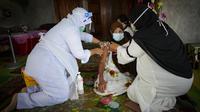 Petugas medis menyuntikan vaksin COVID-19 Pfizer kepada wanita lansia di rumahnya di pedesaan Sabab Bernam, Selangor, Malaysia, Selasa (13/7/2021). Tim medis pergi dari rumah ke rumah di desa terpencil untuk menjangkau warga lansia dalam upaya meningkatkan program vaksinasi. (AP Photo/Vincent Thian