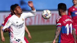Gelandang Real Madrid, Casemiro, berebut bola dengan pemain Elche, Tete Morente, pada laga Liga Spanyol di Stadion Alfredo di Stefano, Sabtu (13/3/2021). Real Madrid menang dengan skor 2-1. (AP/Bernat Armangue)