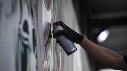 """Seniman menyemprotkan cat saat membuat mural harimau kumbang di Bangkok, Thailand (16/3). Mural tersebut menggambarkan harimau kumbang duduk di sebuah meja """"Perjamuan Terakhir"""". (AFP Photo/Lillian Suwanrumpha)"""