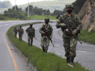 Tentara berpatroli di tengah lockdown yang diberlakukan kembali di pinggiran Bogota, Kolombia, Sabtu (10/4/2021). Kota-kota besar Kolombia memulai akhir pekan pertama lockdown ketat dalam upaya untuk mengurangi penyebaran gelombang ketiga virus corona. (AP Photo/Fernando Vergara)