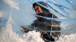 Pemahat es memberikan sentuhan akhir pada patung es di festival Ice and Snow World Harbin, di Harbin, timur laut China, Jumat (3/1/2019). Menjadi acara tahunan, festival es terbesar dunia ini menghadirkan beragam patung es dengan bentuk yang besar dan mewah bagi para pengunjungnya. (NOEL CELIS/AFP)