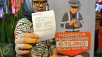 Seorang wanita menunjukkan bukti pembayaran denda tilang dengan tilang online atau e-tilang melalui mesin ATM BRI di Jakarta, Jumat (16/12). Pembayaran elektronik ini sekaligus diklaim bisa menghilangkan praktik percaloan. (Liputan6.com/Angga Yuniar)